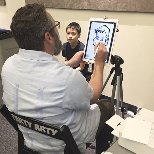 Young man sitting for a digital caricature.