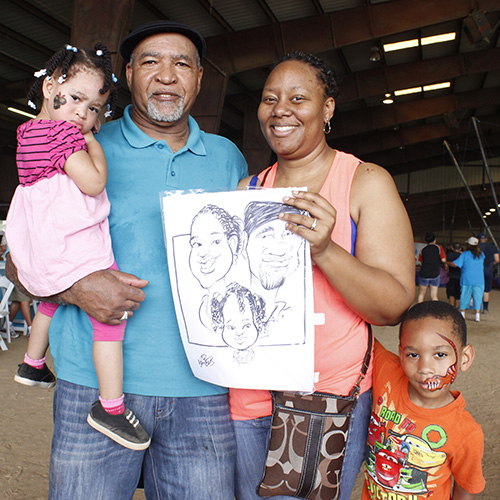 Family holding caricatures of themselves